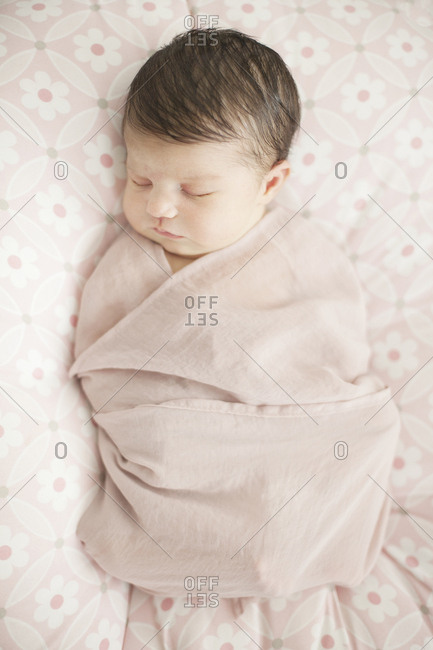 Caucasian baby girl swaddled in blanket