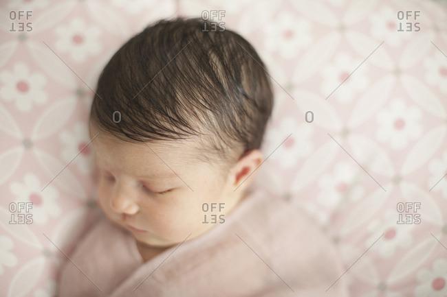 Caucasian baby girl swaddled in blanket
