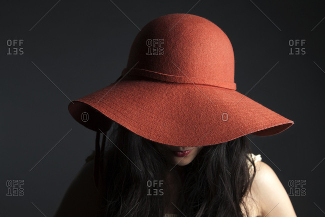 Asian woman hiding behind red hat