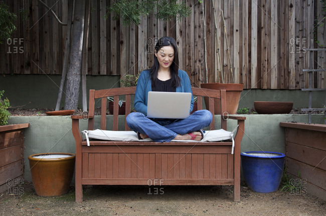 Korean woman using laptop in backyard