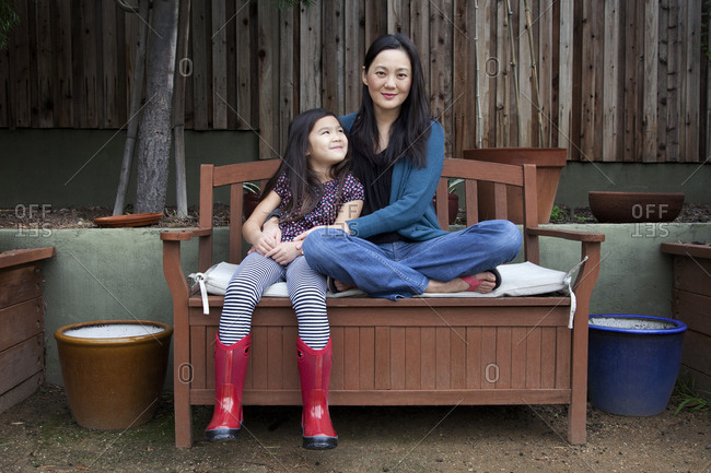 Mother and daughter sitting on bench in backyard
