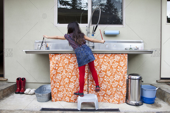 Mixed race girl cleaning paintbrushes in sink
