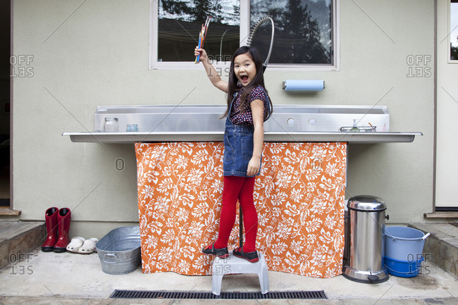 Mixed race girl showing clean paintbrushes at sink