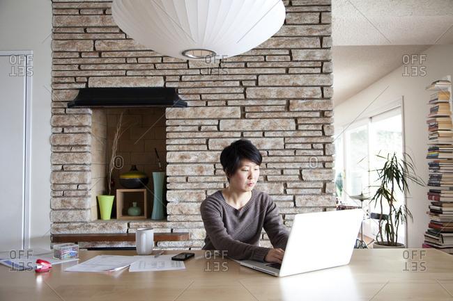 Japanese woman paying bills on laptop