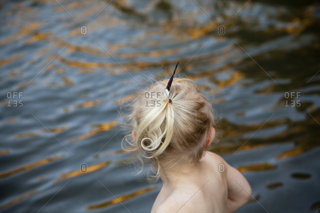 Rear view of girl playing at lake