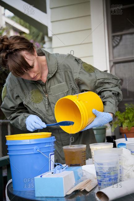 Woman pouring liquid in backyard