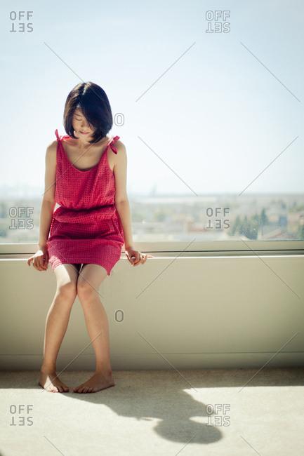 Asian woman sitting in windowsill