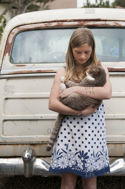 Girl holding cat near vintage car