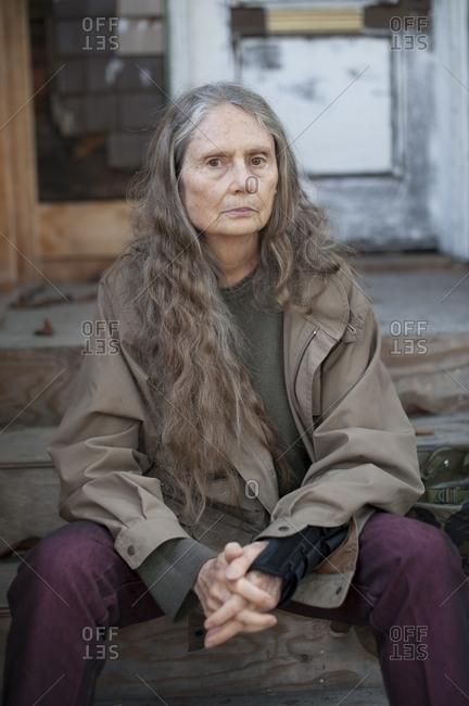 Older woman sitting on wooden front stoop