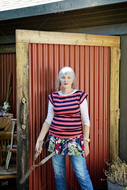 Older Caucasian woman holding shears in backyard