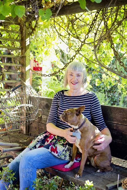 Older Caucasian woman petting dog in garden