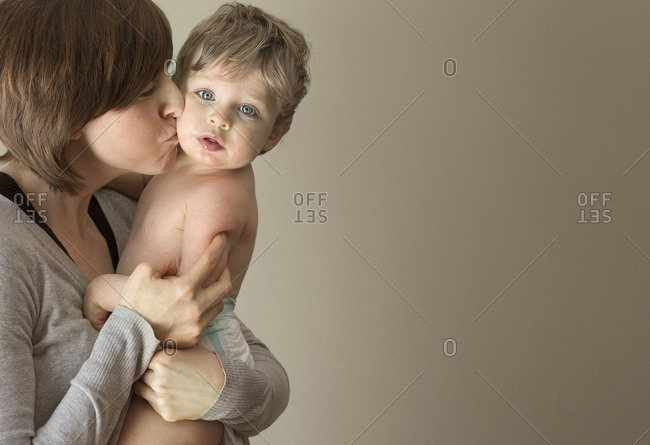 Close up of woman kissing son on cheek