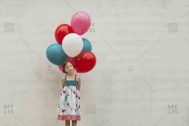 Caucasian girl holding bunch of balloons