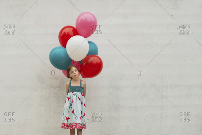 Caucasian girl holding bunch of balloons