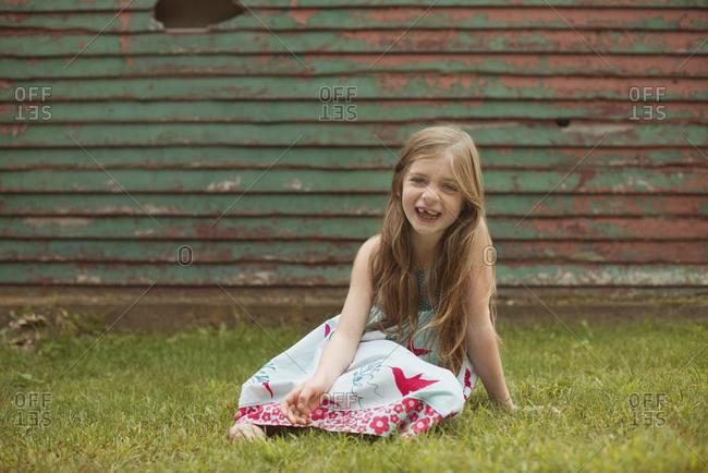 Caucasian girl sitting in backyard