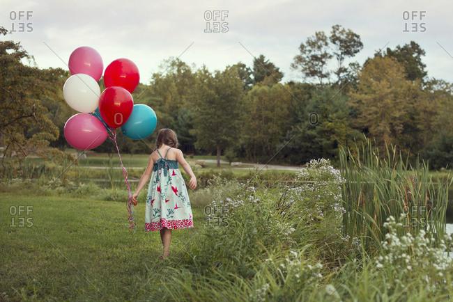 Caucasian girl carrying balloons in rural field