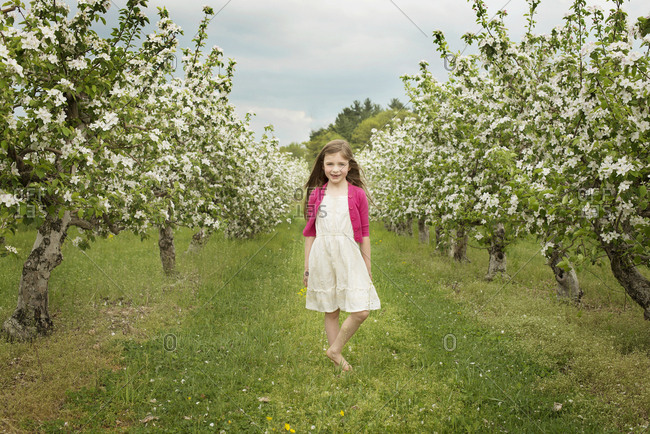 Caucasian girl walking in blooming orchard