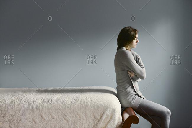 Sad Caucasian woman sitting on bed frame