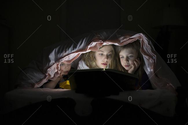 Caucasian sisters using laptop in blanket fort night