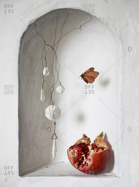 Pomegranate and decorations near moth in wall alcove