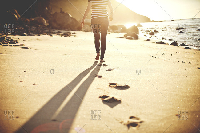 Caucasian teenage girl walking on beach