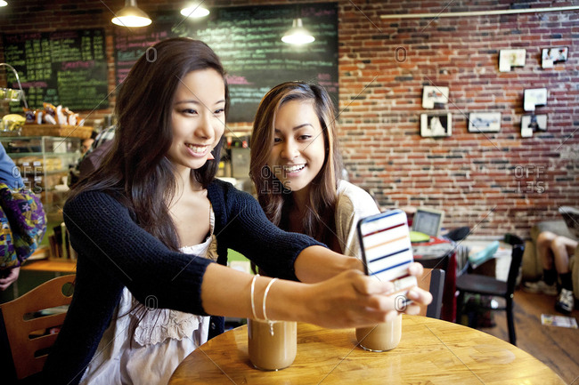 Women taking selfie with cell phone at cafe table