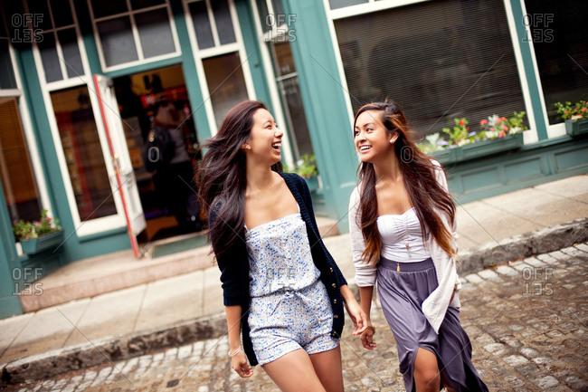 Laughing women crossing cobblestone street