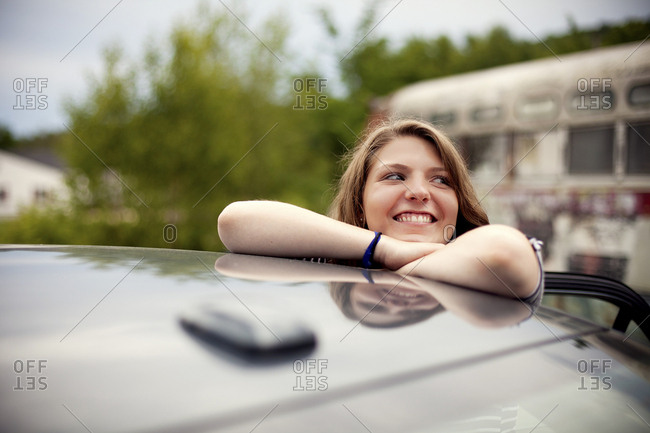Smiling girl leaning on car roof