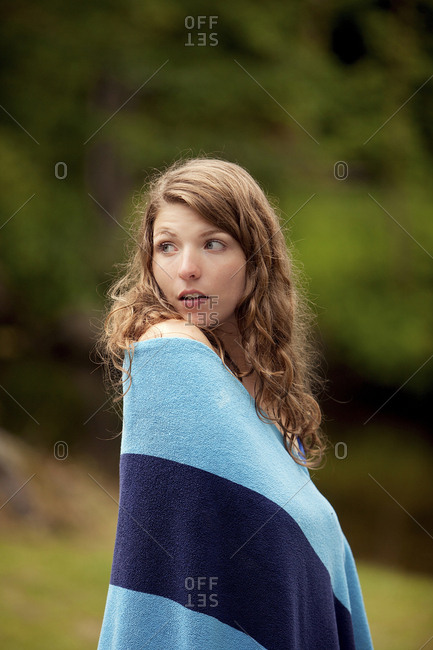 Girl wrapped in blanket in forest