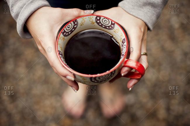 Caucasian teenage girl holding cup of coffee