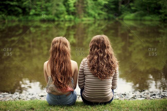 Rear view of girls sitting near lake