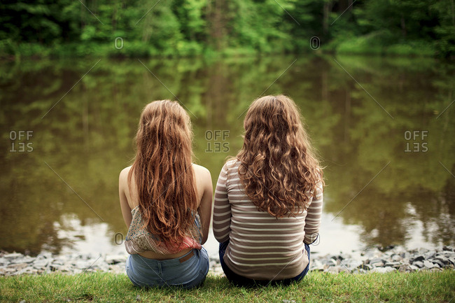 Rear view of girls sitting near lake