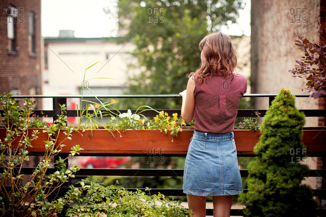 Teenage girl looking out from urban rooftop