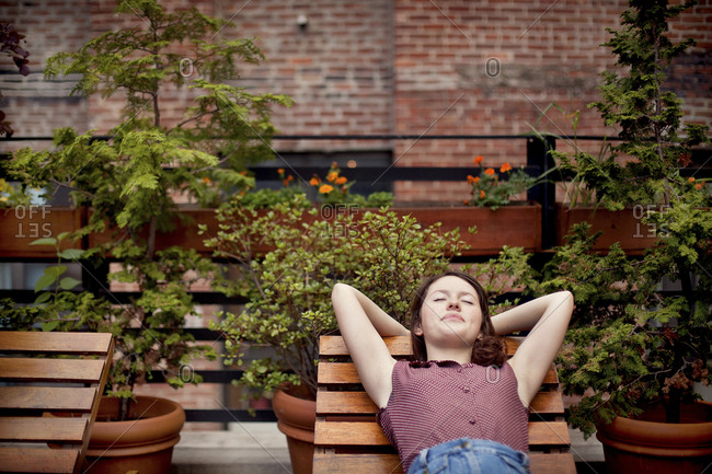 Teenage girl relaxing on urban rooftop