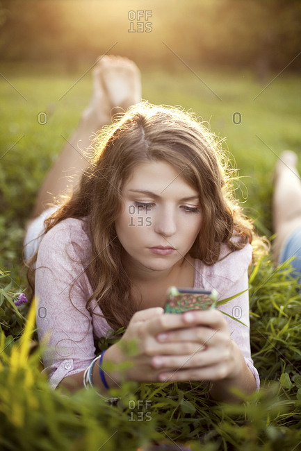 Woman using cell phone in rural field