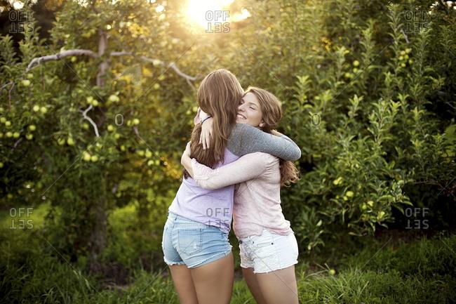 Caucasian women hugging in rural field