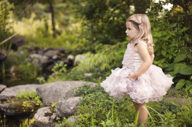 Girl in frilly dress exploring creek