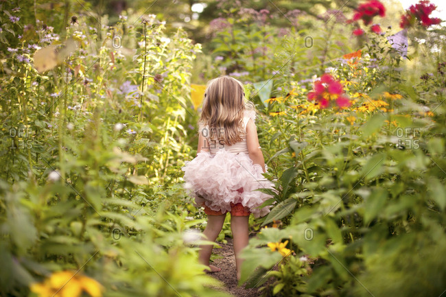 Girl in frilly dress exploring tall flowers