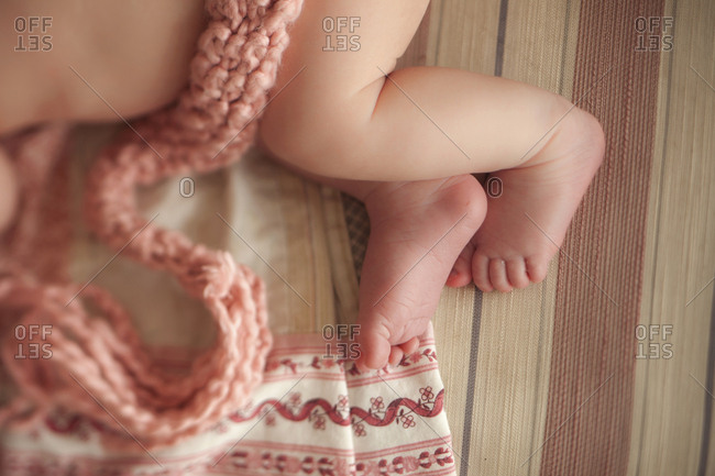 Close up of baby girl laying on knitted blanket