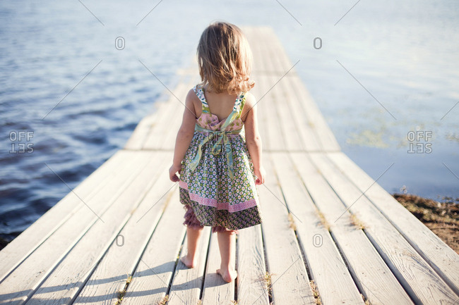 Girl walking on wooden dock over rural lake