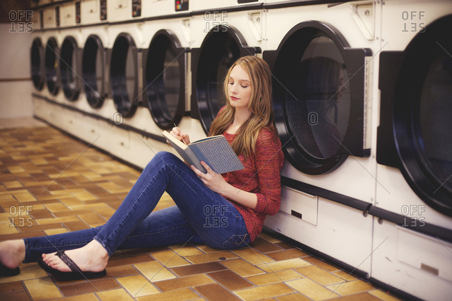 Woman reading book at laundromat