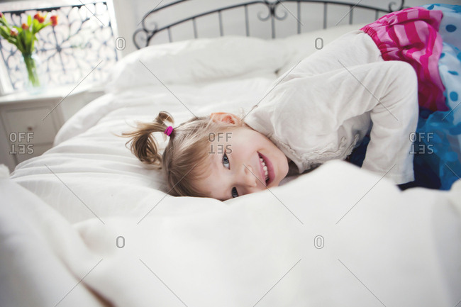 Smiling girl playing on bed