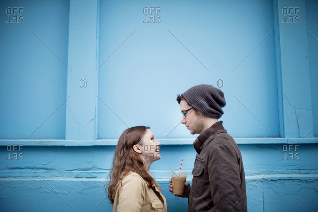 Couple standing near blue wall
