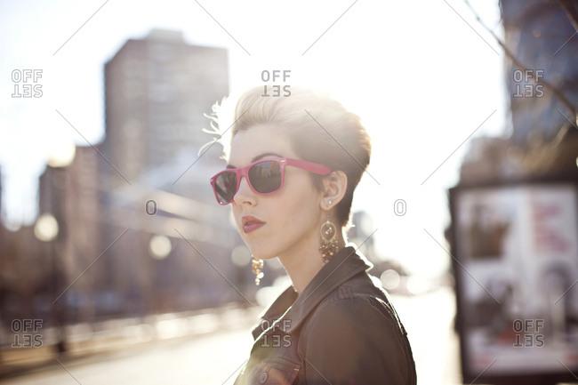 Woman wearing sunglasses on city sidewalk