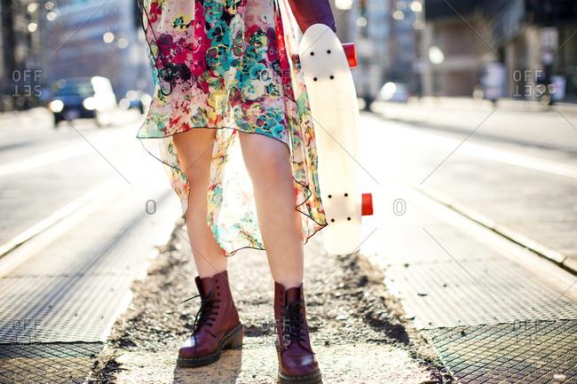 Woman carrying skateboard on city sidewalk