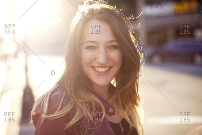 Woman smiling on sunny city sidewalk