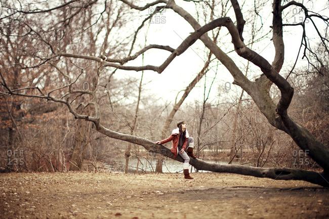 Caucasian woman sitting in tree in rural field
