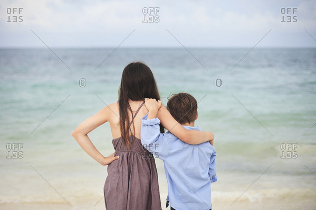 Brother and sister hugging on beach