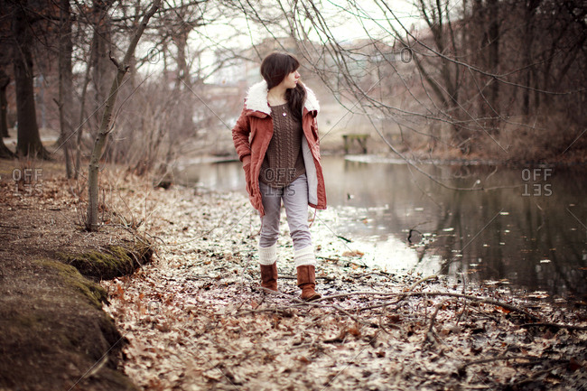 Caucasian woman walking near rural creek