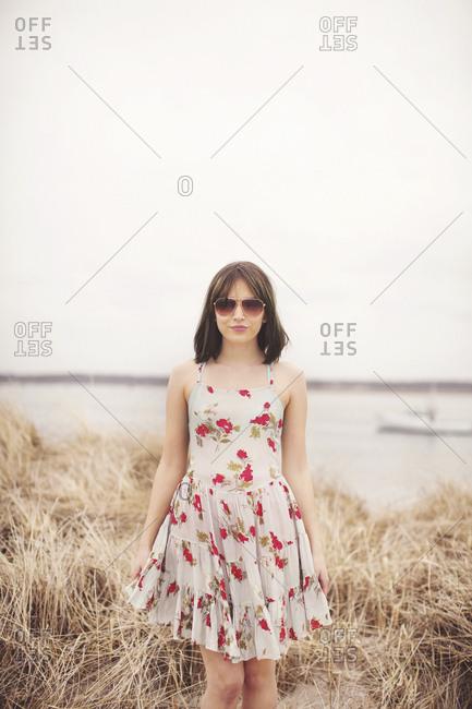 Caucasian woman standing in beach grass